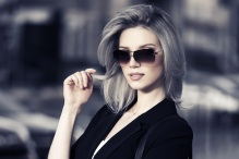 Young fashion business woman in sunglasses on a city street